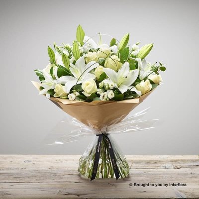 This elegant, contemporary hand-tied bouquet is simple yet stunning. Skilfully created by Sandra's Florist the selection of  white large-headed roses, white Oriental lilies and white lisianthus are beautifully complimented by loops natural material, this truly shows how much you care.