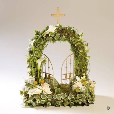 This woodland-style gates of heaven design features ivory large-headed Roses and Calla Lilies, orchids and other material flowers that reflect the natural feel given by this beautiful tribute. The complimenting foliage plays an important feature along with the moss to complete this woodland style design created by Sandra's Florist.