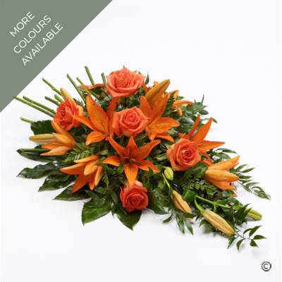 This classic spray is created with Oriental lilies and large-headed roses nestled amongst  Aralia leaves and complimenting dark green foliage. This single ended spray features stem ends to resemble a natural bunch, with the convenience of being arranged into floral foam to ensure longevity.  The design is available in the colours of: orange, Pink, White and Yellow and white. This beautiful design will be carefully created and hand delivered by Sandra's Florist.