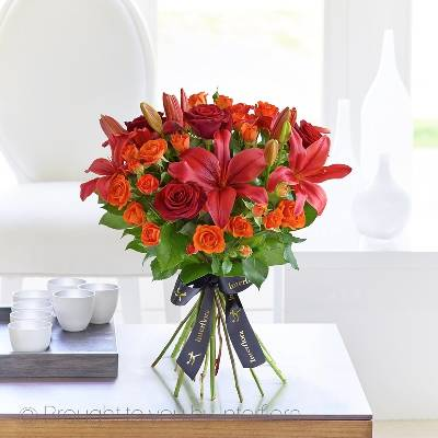 The rustic orange, rich reds and lush greens in this sumptuous bouquet give it a real warmth and elegance. This classic combination of carefully selected roses and lilies is sure to delight someone special.  Featuring large-headed Grand Prix red roses, orange spray roses, red Asiatic lilies and of set with dark green foliage, Sandra's Florist will expertly hand-tied and presented in luxurious packaging for maximum impact when your gift is delivered.