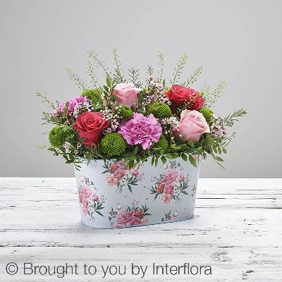 This stunning Mothers Day arrangement is hard to beat. Featuring pink large headed roses, cerise large headed roses, cerise carnations, green spray chrysanthemum and pink waxflower with thlaspi, salal and pistache, presented in a floral patterned tin. It's a beautiful gift that is ready to display and enjoy as soon as it arrives carefully hand delivered by Sandra's Florist.