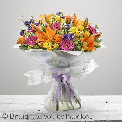 Bring a dazzling smile to her face with this wonderfully cheerful bouquet of fresh flowers. This stunning handtied bouquet will be skilfully created by the Sandra's Florist team and features orange LA lilies, orange roses, purple lisianthus, green bupleurum, yellow spray roses and cerise germini with salal, hand-tied, wrapped and presented in gift packaging, this is an enchanting display that will look stunning in any room.