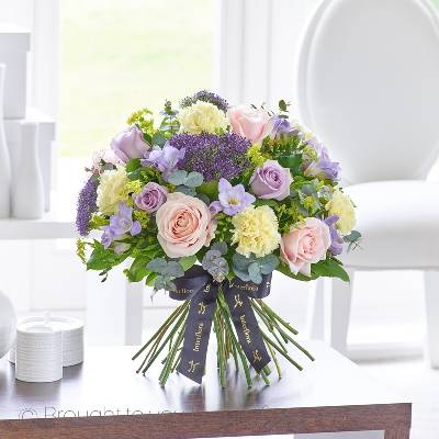 This magnificent hand-tied bouquet of the very finest, premium quality flowers is a luxurious choice that retains a sense of stylish informality too. If they love flowers, they're guaranteed to feel very special receiving this thoughtful gift in pretty tones of pink, cream and Lilacs.  Featuring Cream carnations, premium pale pink Avalanche large headed roses, lilac large headed roses, lilac Blue Moon freesia and lilac Blue Lane trachelium with bupleurum and complimenting foliage, expertly hand-tied by Sandra's Florist and presented in luxurious packaging for maximum impact when your gift is delivered.