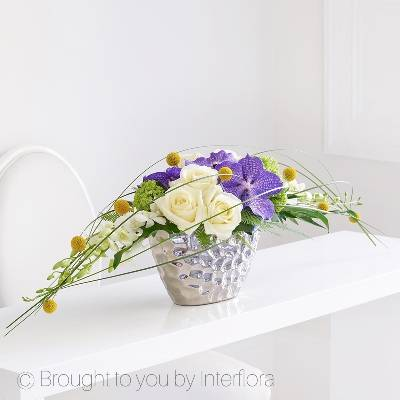 This immaculately presented arrangement is designed as a streamlined statement piece. Bringing together the latest trends in floral sophistication, vibrant vanda orchid heads contrast with blowsy roses and simple craspedia in a wide, free-flowing shape, interspersed with layers of ivory Dendrobian orchids and steel grass which form a natural canopy across this beautiful arrangement skilfully hand made by Sandra's Florist, Holbury.