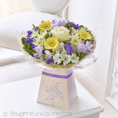 We've chosen this selection of pretty flowers in cool shades of lemon and lilac to celebrate the arrival of a bouncing baby boy. Carefully arranged by Sandra's Florist and beautifully presented in this cute box, this gift is a charming gift choice for any new parent.