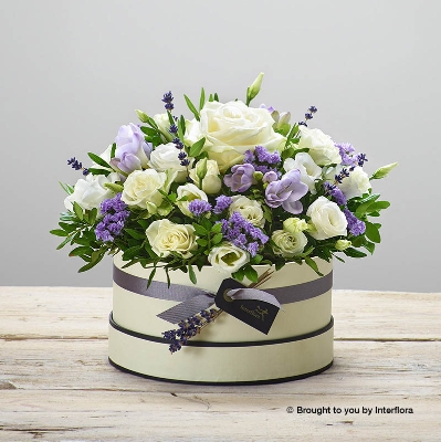 This hatbox is a beautiful designs that features white spray roses, a white large headed rose, purple freesia, white double lisianthus, purple statice, dried lavender and complimenting foliage   Sandra's Florist will skilfully arrange the beautiful fresh flowers into in a soft nude hatbox, trimmed with ribbon.