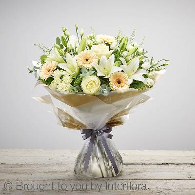 This is a stunning soft coloured hand tied bouquet will be skilfully created by Sandra's Florist for the perfect gift. It features Featuring ivory large headed roses, white lisianthus, white spray roses, white LA lily, peach germini and complimenting foliage. It's finished and presented with beautifully gift packaging.