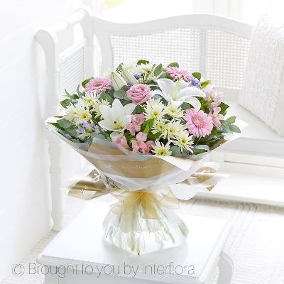 This glorious hand-tied bouquet is wonderfully feminine and exudes a sense of timeless elegance and beauty. We, at Sandra's Florist, love the array of textures plus the shades of soft pink, fresh white and cool lilac, each adding something new to admire. An irresistible gift.