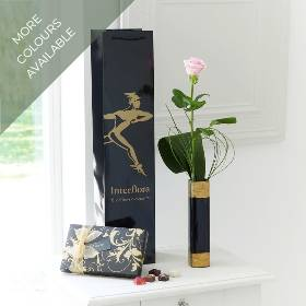 This simple gift is a great gift, with something for all the senses! We've chosen elegant bear grass and an aspidistra leaf as the perfect complement to a single long-stemmed pink rose presented in a stylish black vase. Plus, this gift is carefully hand delivered by Sandra's Florist in a gift bag with a box of luxury Maison Fougère Belgian chocolates, an ideal as a treat for someone special.