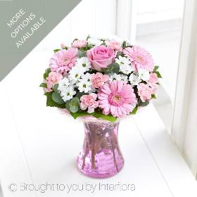 This vase full of pretty pink and white flowers really is the perfect gift. Sandra's Florist have created it so it's all ready to display, easy to look after and it's filled with a selection of favourites. Featuring a pink large-headed rose, pink germinis, white spray chrysanthemums and pink spray carnations with complimenting foliage, presented in a curved glass vase with pink sisal collar.