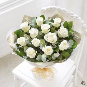 Sending a dozen White Roses is a truly beautiful gift! You can relax in the knowledge that Sandra's Florist will select twelve of the finest, large-headed white Roses to create a hand-tied bouquet guaranteed to take their breath away.