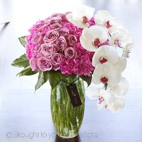 The height of sophistication, this striking vase arrangement is a magnificent gift choice. Two exquisite stems of Phalaenopsis orchid are perfectly contrasted by a bed of superb carnations and large-headed roses in pink and lilac tones. This lavish vase arrangement hand created by Sandra's Florist is a pleasure to behold.  Featuring two stems of white Phalaenopsis Orchid with premium roses and Farida carnations expertly hand-tied and arranged in a glass crackle vase. This gift is presented in luxurious packaging for maximum impact when your gift is delivered.