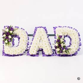 A mass of white double spray chrysanthemums is used to create the perfect base for delicate sprays with a selection of flowers including roses and lisianthus in white and purple. This Dad tribute is framed with complimenting ribbon and will be carefully created and hand delivered by the experts at Sandra's Florist.