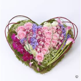 This striking heart-shaped design including large-headed Roses, Carnations and Orchids. Sandra's Florist achieve the contemporary feel with sweeping pink Calla Lilies the cornus and steel grass finish off this tribute with a truly three dimension feel ensuring it's a beautiful tribute for you to give.