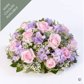 This classic posy arrangement is created with roses and scented freesia nestled amongst choice foliage. Sandra's Florist can create this tribute in two colour tones: pink and lilac or yellow and white.