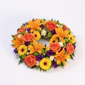This beautiful tradition wreath is made from a selection of luxury flowers and available in three colour options: Pink and Lilac, white, or vibrant. The tribute includes Lilies and large-headed roses, lisianthus and  along with other flowers and complimenting foliage in this circular wreath.