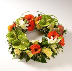 An elegant wreath featuring an exotic mix of anthuriums, calla lilies, gerberas, lilies and carnations accompanied with tropical foliage and looped elegant grass that gives the tribute a contemporary feel. Sandra's Florist can create this striking design in two colour options: White, Peach, green with a touch of orange, or Orange, green and white.