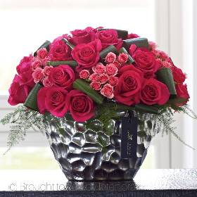 A true statement piece, this designer floral arrangement in luxurious shades of darkest pink and coral is a glorious canopy of the most stunning flowers. An abundance of vibrant large headed roses and delicate spray roses with glossy green aspidistra makes this is a deluxe gift of fresh flowers.  Featuring a generous selection of large headed pink roses with pink spray roses, contrasting textural foliage including aspidistra leaves, all expertly arranged by Sandra's Florist in an elegant silver ceramic container for maximum effect.