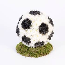 A mass of white double spray chrysanthemums are used to create this football-themed three dimensional tribute. To add realism to the football tribute Sandra's Florist will spray sections black to create the distinctive football patch pattern. The tribute is then displayed on a moss-covered base.