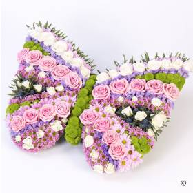 An array of pinks, lilacs, lime green and white make up this beautiful butterfly-shaped floral tribute. Sandra's Florist will carefully create this striking design featuring spray chrysanthemums, pink and white roses, blue eryngium, lilac statice and lime green spray chrysanthemums.