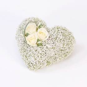 This graceful simple heart shaped tribute is perfectly delegate. Three perfect cream large-headed roses are arranged by Sandra's Florist with simple grass amongst a bed of carefully massed white gypsophila flowers for a tribute that is very special.