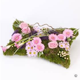 This pillow-shaped design has a natural woodland theme and includes pink large-headed roses, germini and spray chrysanthemums along with calla lilies and twisted hazel amongst an array of greenery. Sandra's Florist will skilfully arrange and hand deliver this beautiful tribute with care.