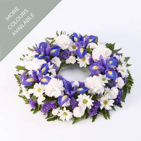A traditional circular wreath arranged with a classic selection of flowers including carnations, Iris and spray chrysanthemums and complimenting foliage. Skilfully arranged by Sandra's Florist and carefully hand delivered.