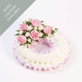 A classic circular wreath bedded with a mass of white double spray chrysanthemums to give the perfect base for a spray of roses and spray roses, the tribute is finished with a coordinating ribbon.  This funeral designs is available in pink and white and red and white.