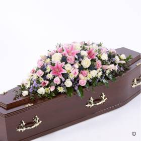 A selection of pink and white roses are arranged with stunning pink Oriental lilies, blue eryngium, white spray chrysanthemums, lilac September flowers and a selection of foliage to create this beautiful casket spray. The tribute will be skilfully arranged by Sandra's Florist and carefully hand delivered.