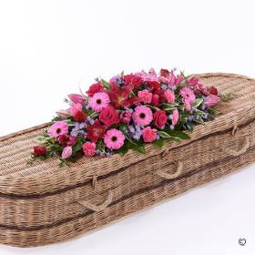 This striking casket spray features a classic selection of flowers including large-headed Rose, carnations, Gerbera and Oriental Lilies. The colour combination of pink and red is lifted by the touch of  lilac and complemented by the green luxurious foliages. Sandra's Florist will carefully create and hand deliver this coffin spray that can adorn all type of funeral casket.