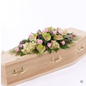This distinctive coffin spray brings together the soft green shades of cymbidium orchids and green anthurium, with delicate pink calla Lily, veronica and large-headed Rose. The spray will be skilfully created by Sandra's Florist with the striking flowers complimented with a selection of foliage including aspidistra, aralia leaves, palm leaves and elegant grass.