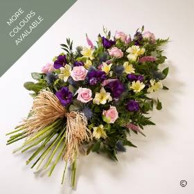 This beautiful tribute has a natural look and feel. It includes large-headed roses, lisianthus, alstroemeria and veronica along with luxury foliages and a natural ribbon bow. It is available in different colour tones of:  pink lemon and blue, Yellow and blue and Vibrant colours. Sandra's Florist will carefully create and hand deliver this attractive woodland spray.
