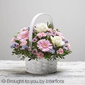 We've filled this classic white basket with stunning fresh flowers to create a sumptuous gift. Your Mum will love the exquisite selection of flowers skilfully arranged by Sandra's Florist.  Featuring white large headed roses, pink spray carnations, pink spray chrysanthemum, pink germini and lilac statice with salal and pistache, beautifully arranged in a white circular softwood basket.