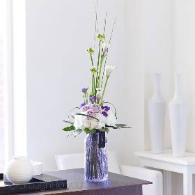 This beautiful tall design of white, lilac and purple shades is sure to make a lasting impression on someone special. The purple crackled vase compliments the flowers wonderfully and gleams in the light from all angles.  Sandra's Florist will skilfully create this design that features calla lilies, white hydrangeas, lilac large headed roses, white ornithogalum and purple lisianthus, with the use of glossy large leaves, striking grass, this breath-taking design will be arranged in a purple crackled glass vase with Luxury Gift Packaging for maximum impact.