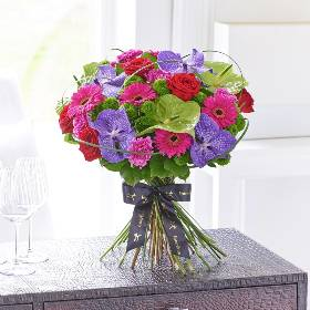 This modern hand-tied bouquet of the very finest, premium quality flowers is a luxurious choice that retains a sense of stylish informality too. If they love flowers, they're guaranteed to feel very special receiving this thoughtful gift in pretty tones of purple, cerise, red and fresh lime.  Featuring Blue Magic Vanda orchid heads in individual hydrating tubes, green Midori anthurium, cerise St Farida carnations, cerise germini, red Naomi large headed roses and green Feeling Free spray chrysanthemums with elegant grass and complimenting salal foliage. Sandra's Florist will expertly hand-tied and present the bouquet in luxurious packaging for maximum impact when your gift is carefully hand delivered.