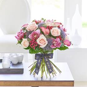 This Chic contemporary hand-tied bouquet of the very finest, premium quality flowers is a luxurious choice that retains a sense of stylish informality too. If they love flowers, they're guaranteed to feel very special receiving this thoughtful gift in pretty tones of pink, Cerise and Lilac.  This breath taking bouquet features stunning pink calla lilies, beautiful pink cymbidium orchid heads in individual hydrating tubes, pale pink large headed roses, lilac Blue trachelium and Cerise bouvardia with eucalyptus and salal, expertly hand-tied and presented in luxurious packaging for maximum impact when your gift is carefully hand delivered by Sandra's Florist.