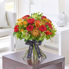 This contemporary hand-tied bouquet of the very finest, premium quality flowers is a luxurious choice that retains a sense of stylish informality with a touch of the tropics. If they love flowers, they're guaranteed to feel very special receiving this thoughtful gift in tones of Red, Orange and fresh lime, skilfully created by Sandra's Florist.  Featuring the best quality orange calla lilies, green cymbidium orchid heads in individual hydrating tubes, glossy green hypericum, red Naomi large headed roses, orange spray roses and orange leucospermum with bupleurum and salal, expertly hand-tied and presented in luxurious packaging for maximum impact when your gift is hand delivered.