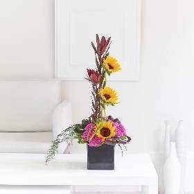 This vibrant designs created by Sandra's Florist includes sunflowers and hot pink carnations, it combines fantastic colours and a range of textures for a striking take on a traditional form.