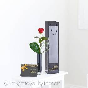 Often less is more, this simple gift set is a great way to show your feelings. We've chosen elegant grass and an aspidistra leaf as the perfect complement to a single long-stemmed red rose. Sandra's Florist will present it in a stylish black glass vase, it will be carefully hand delivered in a gift bag with a box of luxury Belgian Chocolates.
