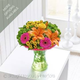 This is a gift of flowers that is simply bursting with glorious colour. Sandra's Florist have created it so it's all ready to display, easy to look after and it's filled with hot pink germini blooms, lime green chrysanthemums, a sumptuous rose and not forgetting the brightly coloured lilies and complimenting foliage, presented in a curved glass vase with blue sisal collar.
