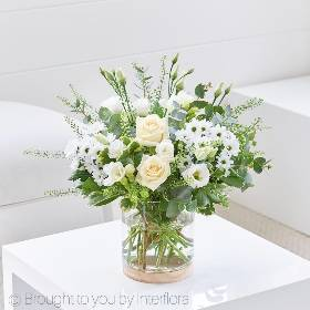 This elegant selection of crisp white fresh flowers creates a contemporary designs that features cream large headed roses, white lisianthus, white freesia and white spray chrysanthemums, arranged with complimenting foliage. Sandra's Florist will create the design into this contemporary glass vase with a detachable wooden base, a gift in it's own right.