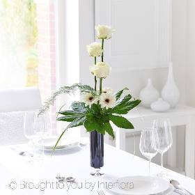 This gorgeous vase arrangement is all about understated elegance. Sandras Florist will select pristine white long-stemmed roses and simple germini with dark contrasting centres form the perfect partnership. Set against constrasting shimmering green leaves and delicate foliage, the result is pure class.