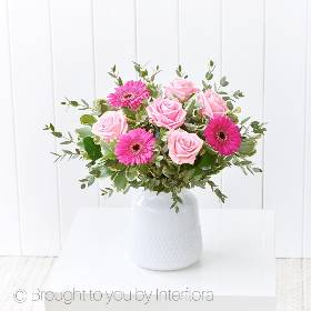 This striking pink vase arrangement is both beautiful and fun. Sandra's Florist will arrange pink large headed roses and cerise germini, with complimenting foliage into a contemporary white glass vase that is a gift in it's own right.