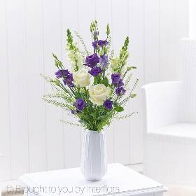 Simply striking this beautiful vase will be created by Sandra's Florist and feature white large headed roses, white antirrhinums and purple lisianthus, arranged with delicate foliage in a tall white ceramic vase, that makes for a lovely keep-sake and gift in its own right.