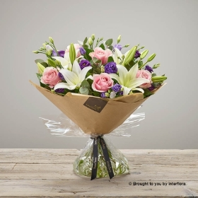This striking elegant handtied bouquet features pink large headed roses, white LA lilies and purple lisianthus with complimenting foliage. Sandra's Florist will skilfully create this this breath-taking bouquet using the finest quality flowers  and beautifully gift-wrap for the perfect gift.