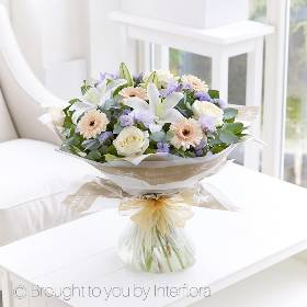 Sophistication, beauty and understated elegance; this exquisite bouquet really has it all. It featuring delicate scented freesias, peach germini, lilac statice, white Oriental lily and large headed ivory roses with complimenting foliage. Sandra's Florist will skilfully create it before beautifully gift wrapping it and carefully delivering it by hand.