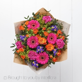 Our exquisite Blooming Brights hand-tied bouquet makes the perfect gift for any occasion. We'll skilfully create this at Sandra's Florist use a variety of beautiful blooms to create this stunning hand-tied bouquet, which is lovingly wrapped and finished with luxury ribbon.  This bouquet includes cerise carnation, cerise germini, blue iris, orange roses, yellow solidago and orange roses. To perfectly compliment these bright blooms, we add complimenting foliage.