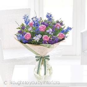 Artistically designed to capture the feeling of a classic English garden, with a contemporary twist. At Sandra's Florist we'll carefully create our Precious Periwinkle hand-tied bouquet using fresh flowers in shades of purple and pinks. This floral bouquet includes purple fressia, purple lisianthus, pink roses and blue delphinium, with green foliage and natural birch added for texture.  Our Precious Periwinkle hand-tied bouquet is popular to send for any special occasion, and makes a beautiful talking point in any home.