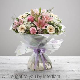 This stunning handtied bouquet will be skilfully created by the Sandra's Florist team.  It features pink large headed roses, pink LA lilies, peach germini, white spray chrysanthemum and pink alstroemeria, with pink waxflower and salal, hand-tied, wrapped and wrapped and presented with beautiful gift packaging.