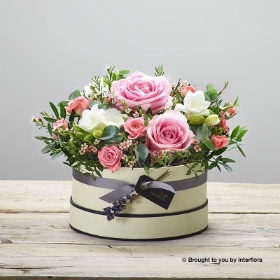 This beautifully presented hat box is skilfully arranged by Sandra's Florist and delivered by hand. Featuring pink large headed roses, pink spray roses, white freesia, dried lavender, pink waxflower and foliage including eucalyptus, presented in a soft nude 'keepsake' hatbox trimmed with ribbon.
